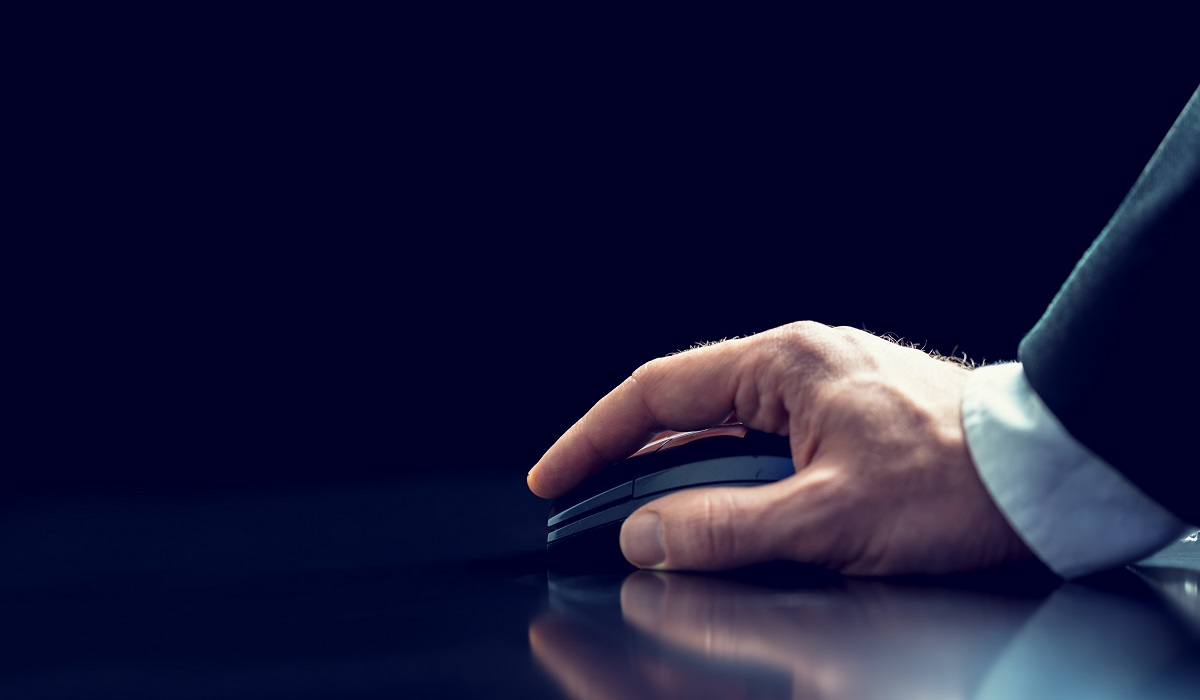 Retro image of the hand of a businessman in a suit using a wireless computer mouse on a reflective desktop against a dark background with copyspace.